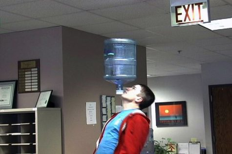Colin Sullivan, junior education major, shows off his routine by balancing a water jug on his chin in the Northern Star newsroom.