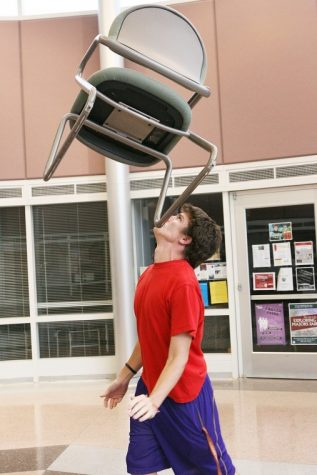 Colin Sullivan, junior physical education major, balances a chair on his chin in the Campus Life Building Thursday evening. Sullivan recently won a nationwide talent show on