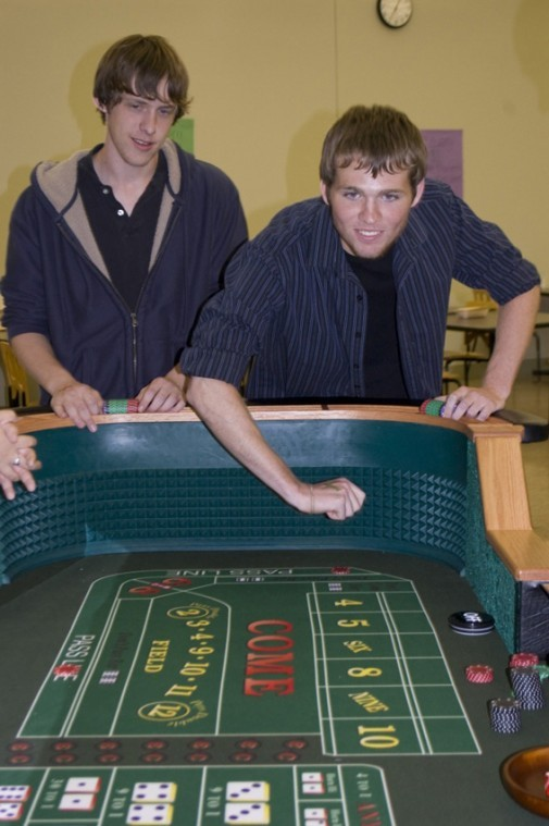 Freshman accountancy major Kevin Haywood (right) takes a roll on the craps table as freshman engineering major Daniel Bankemper looks on during Casino Night in the Stevenson food court Friday night.