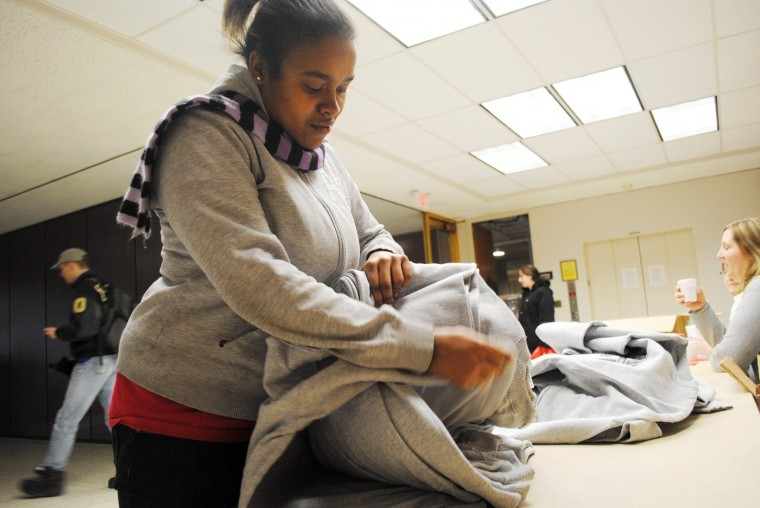 Lichine Williams, sophomore FCNS major, picks out a free sweatshirt at the Winter Resource Fair Tuesday inside the Duke Ellington Ballroom. Students received a free sweatshirt for signing up at six tables at the fair.