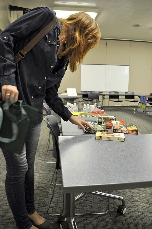 Junior Illustration major, Jaqueline Adamiak looks through books at the Swap Meet in Neptune Central Wednesday. The swap meet helped raise awareness of landfills and promote the reuse and recycling of items.