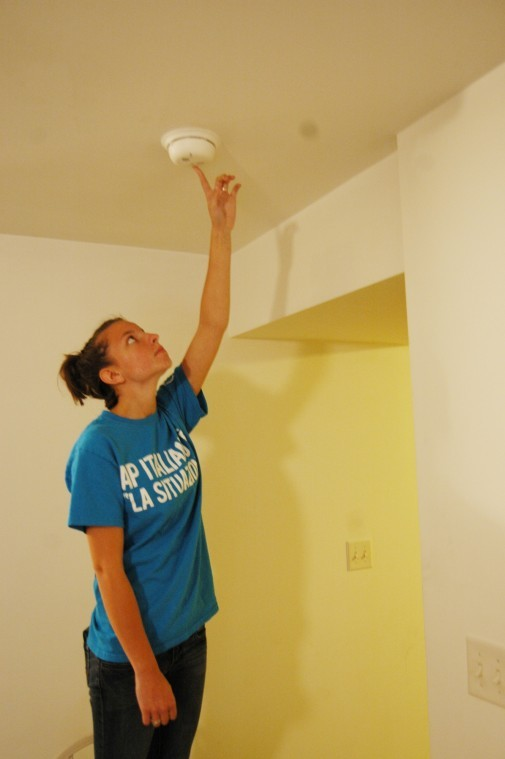 Jennifer Schmitt, sophomore physical therepy major, checks the smoke detector in her townhome Tuesday night.