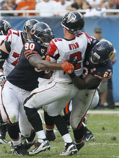 FILE - In this Sept. 11, 2011 file photo, Atlanta Falcons quarterback Matt Ryan (2) gets tackled by Chicago Bears defenders Julius Peppers (90) and Henry Melton (69) just as he released the ball during an NFL football game in Chicago. The Bears won 30-12. The Bears couldnt have asked for much more from their defense after a convincing victory in their season-opener. (AP Photo/Charles Rex Arbogast, File)