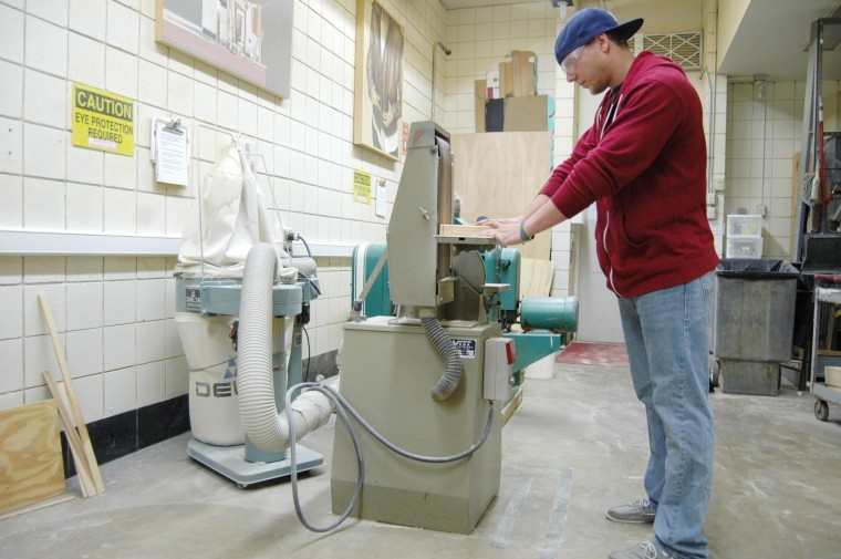 Kyle Myer, junior art education major, sands part of his project in the woodshop classroom in the Jack Arends Visual Arts Building Monday night. The ceiling can leak up to 10 gallons of water on a day with heavy rainfall, woodshop professor Jeremy Gosser said.