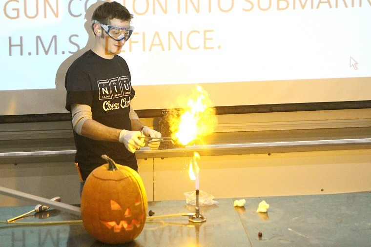 Senior chemistry major Harrison Kuras demonstrates how gun cotton reacts differently than regular cotton when placed to an open flame.