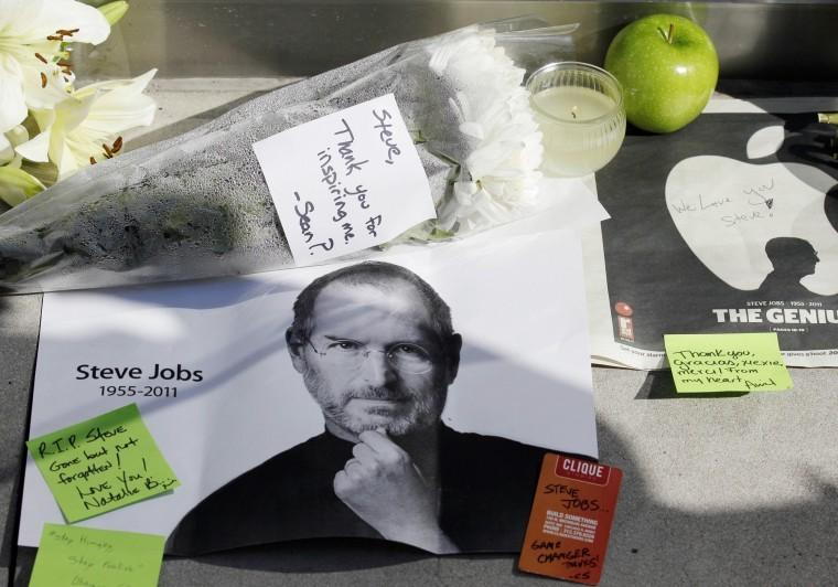 The Associated Press - Flowers, apples and notes are displayed in tribute to Steve Jobs outside of an Apple store in Chicago, Thursday, Oct. 6, 2011. Jobs, the Apple co-founder and former CEO who invented and masterfully marketed ever-sleeker gadgets that transformed everyday technology, from the personal computer to the iPod and iPhone, has died. He was 56.