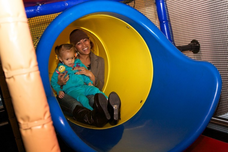 Senior journalism major Brittany Watson goes down a slide with her daughter Haelo, 2, at a McDonald's playground in Sycamore on Sunday.