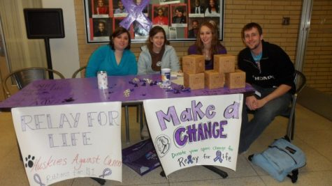 Members of co-ed service fraternity Alpha Pi Omega shout provocative phrases to attract students during a bake sale Thursday. The group is raising money for Relay For Life.