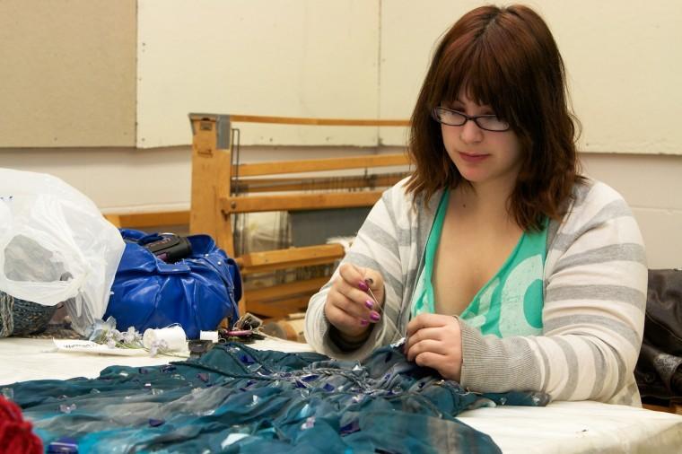 Liz Howell, senior fiber art major, sews glass onto a silk dress that she hopes to finish for her exhibition Friday.