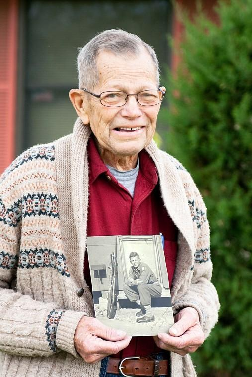 Retired journalism professor Hallie Hamilton holds a photograph taken when he was 19 and first stationed at Fort McClellan, Ala. in 1942.