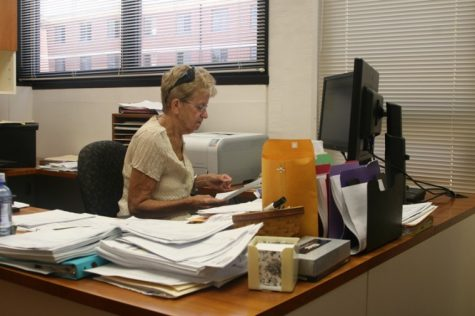Office Manager Pat Siebrasse looks up forms for a faculty member at the School of Family, Consumer and Nutrition Sciences in Wirtz Hall.