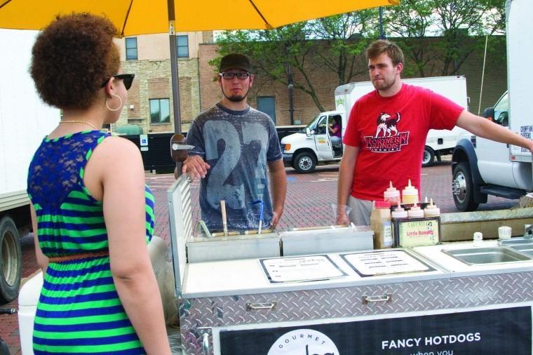 Senior sociology major Jasmine Rogers speaks with hot dog vendors at the DeKalb Farmers Market June 21.