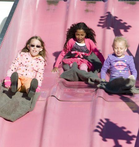 Olivia Thonsend (left)Jennifer Tsaras (center) Jenna Luetkebuenger (right) slides down a giant slide during September Fest at St. Mary's School in DeKalb.
