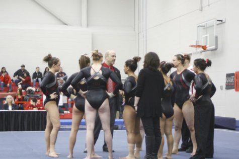 NIU gymnasts gather around to hear Gymnastics Head Coach Sam Morreale give advice during a gymnastics meet.
