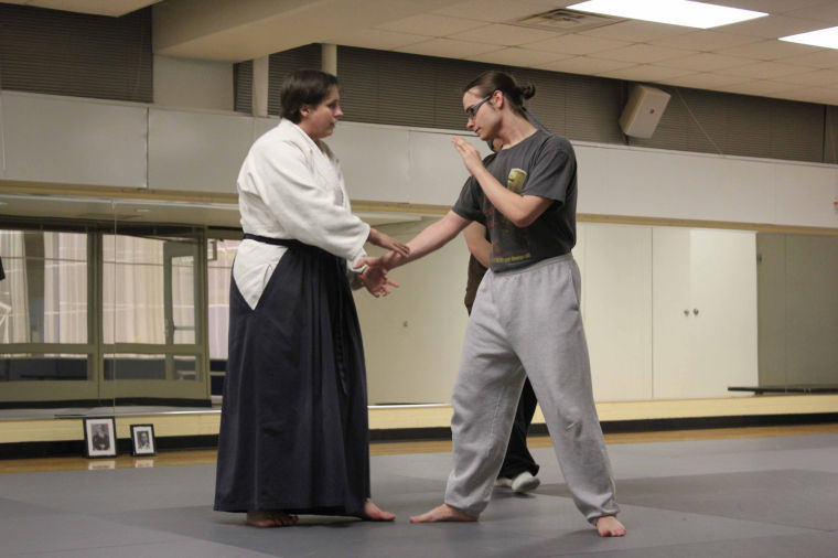 Mathematics graduate student and Aikido instructor Susan Ficken (left) with Junior Mathematics major and NIU Aikido Club Vice President Robert Marks (right) demonstrates a hold and grapple technique at Aikido Club practice in the Chick Evans Field House on Monday night.