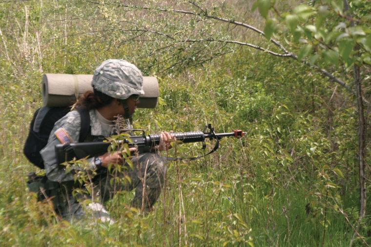 A female ROTC cadet crouches during a ROTC field exercise.