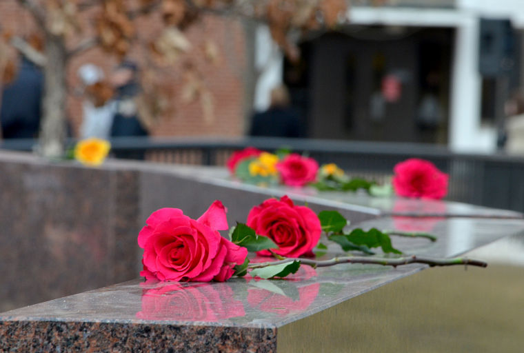 Loved ones of the five victims of the Feb. 14, 2008, shootings put roses on the Cole Hall memorial during the wreath-laying ceremony in 2013.