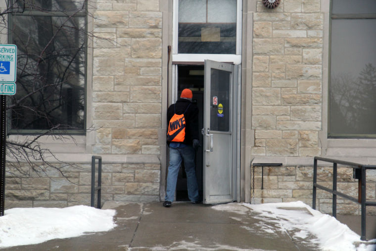 A student walks out of the cold and into Davis Hall during class hours Friday. Some faculty had to adjust the dates of what was planned for class.