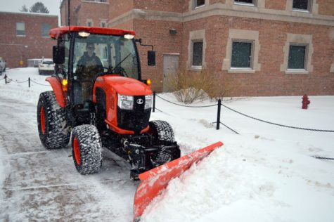 A plow clears snow from the sidewalk between Adams and Williston halls during Monday's heavy snowfall. The temperature is expected to increase within the next couple of days.