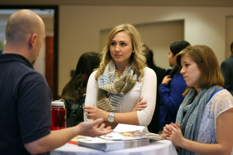 Senior marketing major Laine Smid (left) and sophomore accountancy major Chloe Pooler (right) converse with Rok Teasley of the Peace Corps Monday at Careersfor a CAUSE. The Peace Corps was one of several organizations and businesses that attended Careersfor a CAUSE at the Barsema Alumni & Visitor's Center. The event encouraged students to attend so they could network with companies and executives.