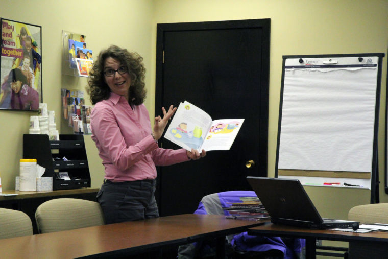 Mary Beth Henning, Center of Economic Education co-director, holds up a children's book called