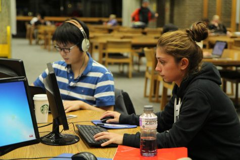 Graduate accounting student Kang Gao (left) and Nino Mebuke, graduate sports psychology student, work on computer workstations Monday night on the second floor of Founders Memorial Library. The university has plans to expand its Wi-Fi, potentially providing it to portions of downtown DeKalb.