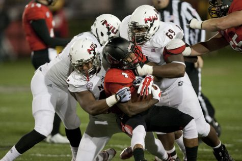 A host of Huskies tackle running back Horactio Banks Wednesday at Scheumann Stadium in Muncie, Ind. The defense forced five turnovers and converted them into 21 points in the 35-21 victory over Ball State.