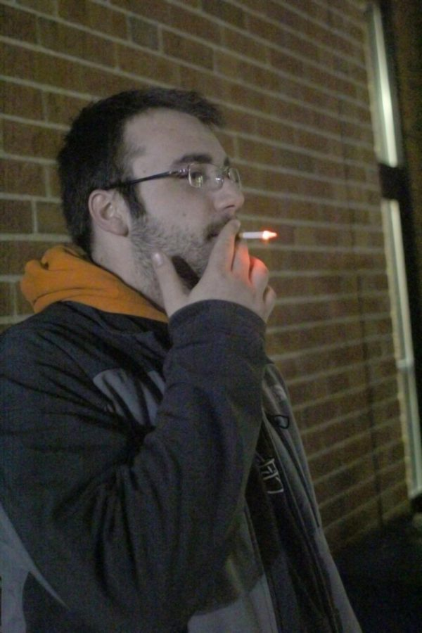 Junior communication major Danny Albers smokes a cigarette outside of DuSable Hall Jan. 22. NIU must implement a campus smoking ban to be compliant with the Smoke-Free Campus Act by July 1.