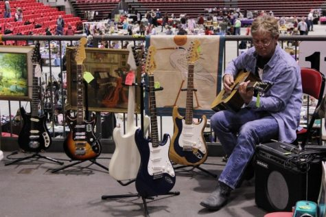 Steve Briarton, 55, of Monroe Center plays guitar at his stall April 22, 2012 at the Colossal Clean Sweep in the Convocation Center.