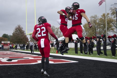 Shane Wimann (35) celebrates a touchdown with fellow receivers Clayton Glasper (81) and Aregeros Turner (22). The Huskies caught four touchdowns in their 49-21 victory over Eastern Michigan on Saturday.