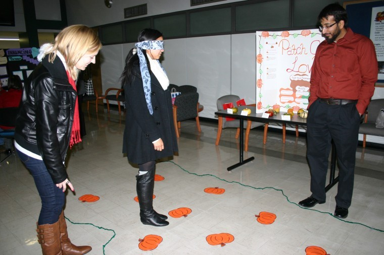 Prospective grad students Erica Bell and Mimi Chiu, 23, direct each other blindfolded through a pumpkin patch in a direct communication exercise conducted by Usmahn Mughni, senior grad student and therapist at the NIU therapy center on Nov. 12, 2012.