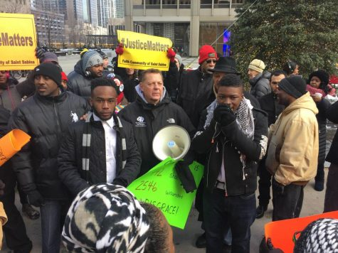 Amirius Clinton (left), junior political science major, stands beside Father Michael Pfleger and other protestors during the Peace March on Dec. 31 in Chicago. Clinton said an unlawful assemblies ordinance by the City Council is in response to past student protests involving NIU students, such as Black Lives Matter protests and the Peace March.