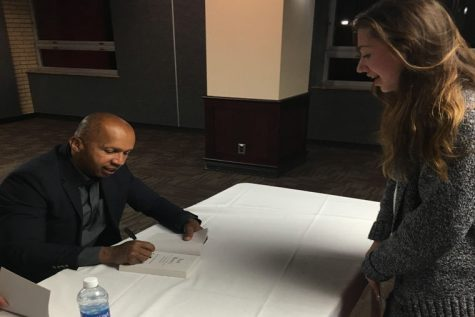"""Author Bryan Stevenson signs his book """"Just Mercy"""" for freshman engineering major Claudia Cruz 6:30 p.m. Monday in the Carl Sandburg Auditorium. """"I've been waiting for weeks for Bryan Stevenson to come to NIU,"""" Cruz said."""