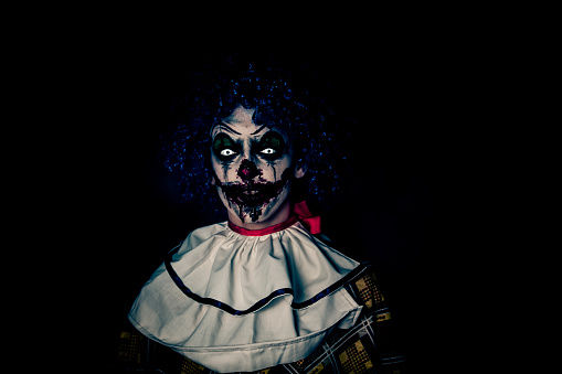 Crazy ugly grunge evil clown on Halloween making people scared