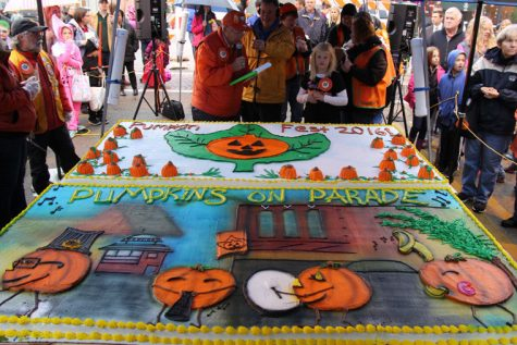 The 55th annual Pumpkin Fest is kicked off by Jarry Malmassar, president of the Pumpkin fest Committee. Malmassar thanks Hy-Vee for the 8 feet cake that will provide up to 1400 to 1600 pieces of free cake for the festival-goers.