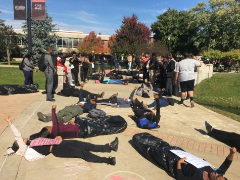Demonstrators made up of Black Student Union members and students lay across a bridge to honor the Black Lives Matter movement outside Cole Hall around noon Tuesday. Some students wore garbage bags to represent those who died and others held signs with information about individuals who died at the hands of police. About 200 students stopped to watch the demonstration.