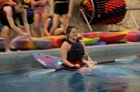 Corina Salinas, junior athletic training major, boards her kayak and lets instructors launch her into the water to begin the kayak pool workshop.