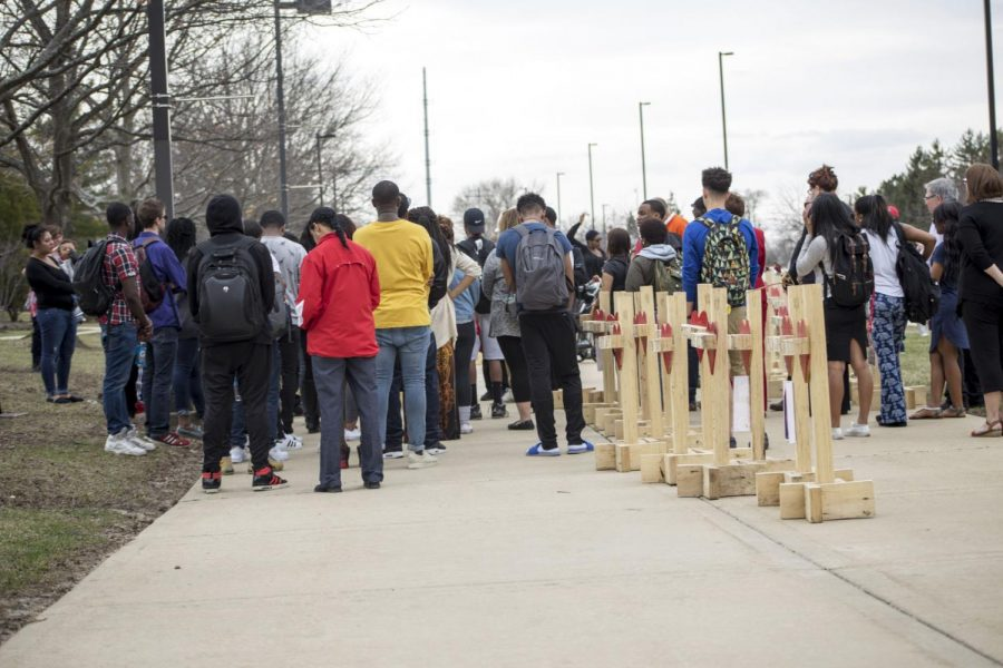 Community members gather to listen to prayer and mourn their loved ones who were killed this year in Chicago. The vigil was held at 3:30 p.m. Friday near the MLK Commons by student groups and Carpenter Greg Zanis.