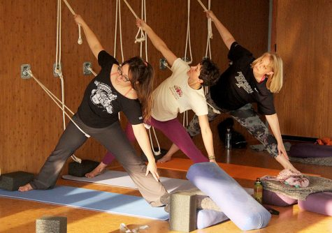 (From left) Rockford community members Allison Hollman, Nicole Messink and Kim White stand in the triangle pose while reaching toward their ankles to stretch their legs and obliques.