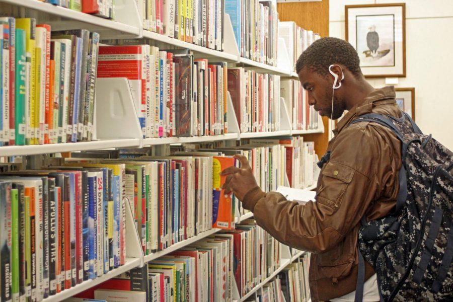 DeKalb resident Hershel Thrower through books at the DeKalb Public Library.