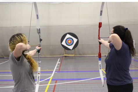 Freshman accounting major Antonia Mendez (left) and junior elementary education major Amanda Childers draw back their bows and aim at a target during the archery meeting Monday.