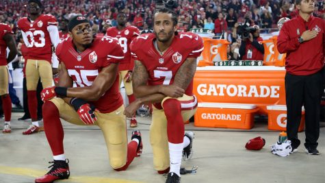 San Francisco 49ers quarterback Colin Kaepernick, left, and teammate kneel during the national anthem before an NFL football game.