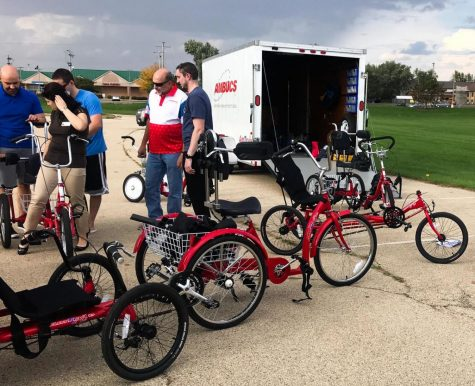 Participants adjust bikes to fit their measurements in demonstrating how to use the adapts-table bikes in the Health, Wellness and Literacy Center parking lot during the workshop Tuesday.