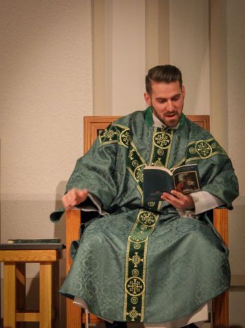 Father Kyle Manno reads and voices a few petitions during the 9 p.m. mass Sunday at the Newman Catholic Student Center, 512 Normal Road.