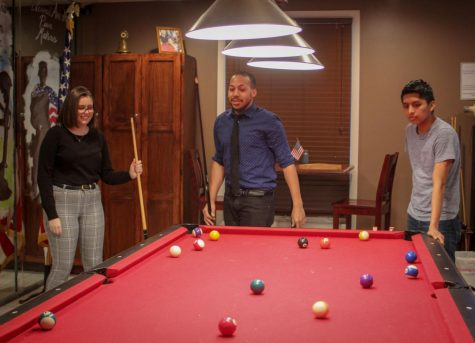 Public Relations Manager Elizabeth Warner (left), co-founder Kwamayne King and Project Phileo co-founder Brandon Soto (right) play pool Wednesday at American Legion, 1204 S. Fourth St.