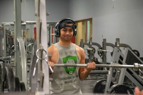 Senior OM&IS major Luis Montenegro works out his biceps at 9 a.m. by using the barebell Wednesday at Fitworkz, 1690 Sycamore Road, in DeKalb.