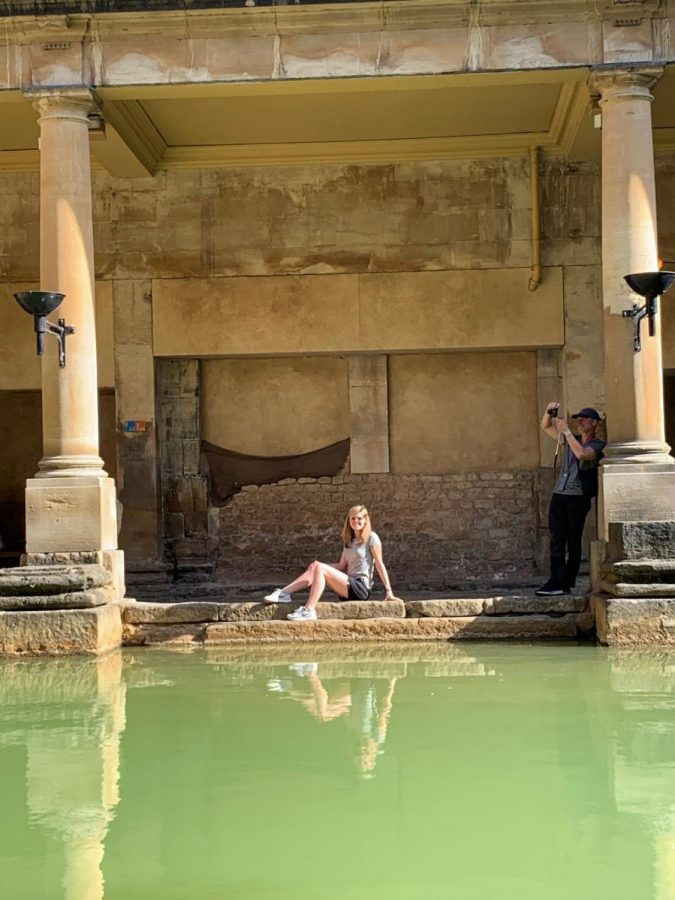 Catherine Carter sits beside Roman baths. The baths are said to have properties that can cure all diseases.
