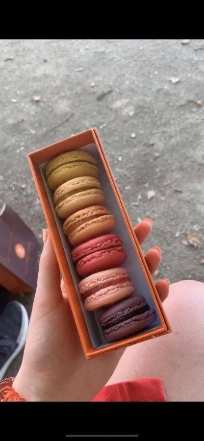 Catherine Carter gets ready to eat brightly colored macarons. She brought them back to England from Paris