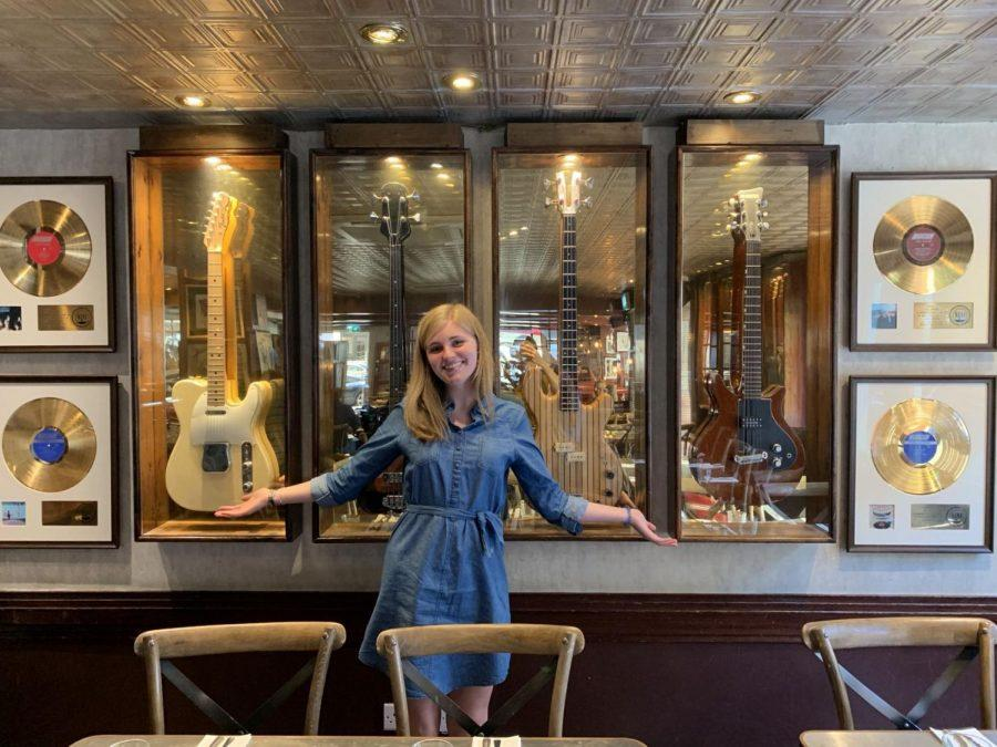 Catherine Carter at a Rolling Stones museum in front of the guitars the Rolling Stones played.