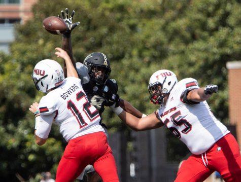 Senior quarterback Ross Bowers makes a throw while being rushed by Vanderbilt defender at Vanderbilt Stadium.